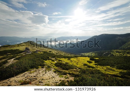 Beautiful mountain landscape. Mountains are visible to the horizon. Cloudy sky with the sun. There is a fog in the valley. The hills covered with grass and forest. No one is around.