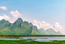 Beautiful mountain landscape of Kui Buri District, Prachuap Khiri Khan province of Thailand. Mountain with water front, blue sky and cloud background, day light landscape.