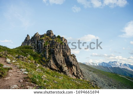 Beautiful mountain landscape with footpath and great sharp rock on hillside. Awesome alpine scenery with pointy crag on background of snowy mountains under blue sky. Trail near big pointed stone. Photo stock ©