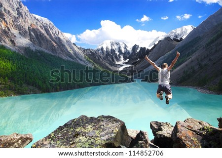 Beautiful mountain landscape with the lake and the jumping man. - stock photo