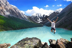 Beautiful mountain landscape with the lake and the jumping man. Sports extreme.