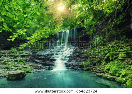 Beautiful mountain rainforest waterfall with fast flowing water and rocks, long exposure. Natural seasonal travel outdoor background with sun shihing #664623724