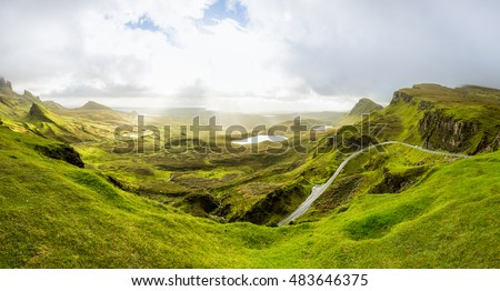 Beautiful mountain range in Scotland. View from the top of Quiraing into the green Valley. Sun beams break through a heavy cloud cover. #483646375