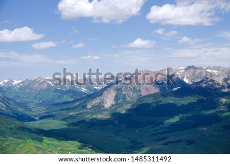 Beautiful Mountain Range Surrounding Crested Butte, CO.  Stunning and Rugged Mountain Peaks with Dynamic Green Valley Beneath.  Cloud Cover Over Beautiful Mountain Peaks. #1485311492