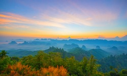 Beautiful mountain range with sky blue and orange light of the sun through the clouds in the sky, Background sky during Sunrise with fog on mountain, Abundant lush forest-Image