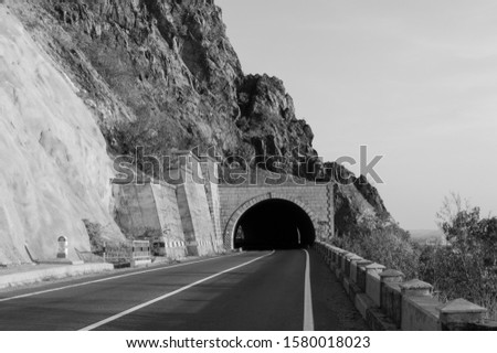 Beautiful mountain road. Road passing through a tunnel covered by mountain ridges. The picture is black and white. Autumn day on the road. No car in traffic. The freeway