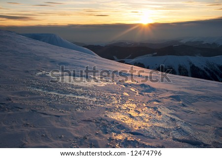 Beautiful mountain sunset landscape with sun way on ice-coated mountainside. (Ukraine, Carpathian Mt\'s, Svydovets Range)
