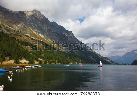 Beautiful mountain Swiss lake. Magnificent sailing yachts are reflected in smooth cold water