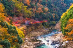 beautiful mountain view in autumn season with sagano scenic railway or romantic train on bridge and boat in the river in Arashiyama, Kyoyo, Japan, soft focus