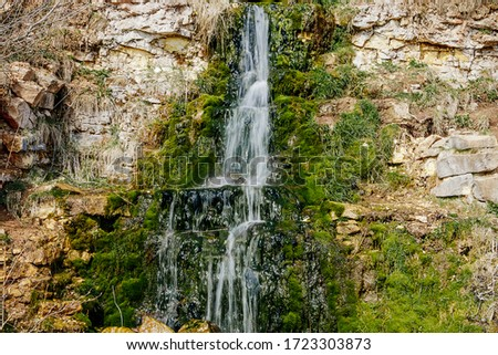 Beautiful mountain waterfall among the stones. A source of water in arid areas. Rocks covered with moss. Motion blur Stock fotó ©