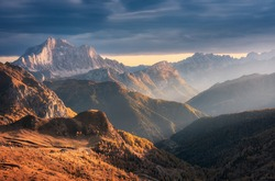 Beautiful mountains at sunset in autumn in Dolomites, Italy. Landscape with rocks, sunbeams, forest, hills with orange grass and trees, blue cloudy sky. Scenery with mountain valley in fog in fall