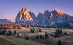 Beautiful mountains with lighted peaks at sunset. Autumn landscape with small wooden houses, mountain valley, meadows with green grass, fall trees, high rocks, sky with moon. Alpe di Siusi in Italy
