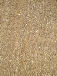 Beautiful multi-colored structure of sand, shells, and seawater. The beach of the Mediterranean Sea, abstraction.