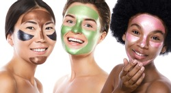 Beautiful multi-ethnic girls with colorful peel-off masks on their faces posing on white background