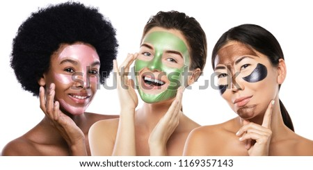Beautiful multi-ethnic girls with colorful peel-off masks on their faces posing on white background #1169357143