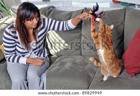 Beautiful multi-racial woman sitting on couch and playing with a cute orange house cat - stock photo