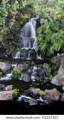 Beautiful multi-tiered waterfall over rocks through lush tropical vegetation.