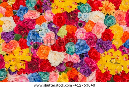 Beautiful multicolored artificial flowers background. flowers decor.