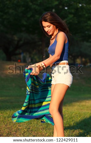 Beautiful multicultural young college woman enjoying outdoor campus life.