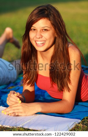 Beautiful multicultural young college woman studying outdoors on campus.