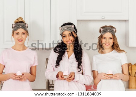 beautiful multiethnic girls in sleeping masks holding cupcakes and looking at camera during pajama party