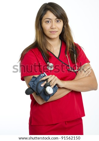 Beautiful multiracial female nurse or physician in red scrubs holding a sphygmomanometer used for determining blood pressure