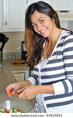 Beautiful multiracial woman in kitchen smiling as she prepares a salad in the kitchen - dropping tomatoes in bowl