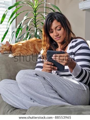 Beautiful multiracial young woman sits on a couch, smiling, in a casual sweater and sweats using an e-reader while an orange cat sleeps behind her