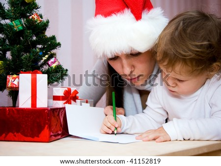 Beautiful mum together with a small daughter write the letter to Santa under a Christmas fur-tree