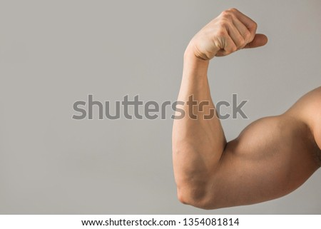 beautiful muscled hand with a muscle on a gray background