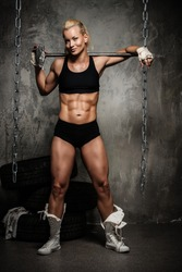 Beautiful muscular bodybuilder woman standing near stack of  tyres with hammer on her shoulders