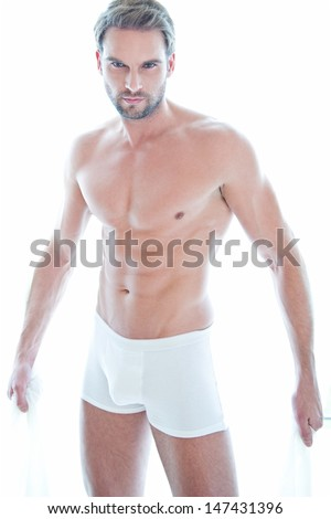 Beautiful muscular shirtless male model with nice abs near window with copy space - in white