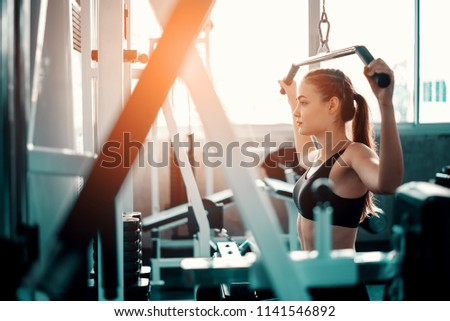 Beautiful muscular sporty caucasian woman exercising building muscle .Young fitness girl execute exercise training with exercise-machine cable cross over in gym ,work out time, horizontal #1141546892