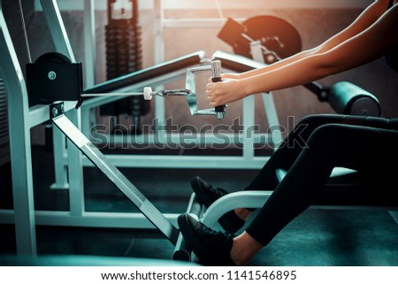 Beautiful muscular sporty caucasian woman exercising building muscle .Young fitness girl execute exercise training with exercise-machine cable cross over in gym ,work out time, horizontal #1141546895