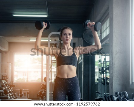 Beautiful muscular sporty caucasian woman exercising building muscle .Young fitness girl execute exercise training with exercise-machine cable cross over in gym ,work out time, horizontal #1192579762