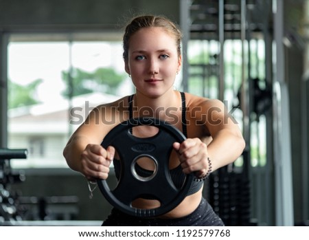 Beautiful muscular sporty caucasian woman exercising building muscle .Young fitness girl execute exercise training with exercise-machine cable cross over in gym ,work out time, horizontal #1192579768