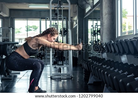 Beautiful muscular sporty caucasian woman exercising building muscle .Young fitness girl execute exercise training with exercise-machine cable cross over in gym ,work out time, horizontal #1202799040