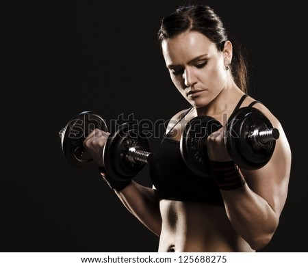 Beautiful muscular woman doing a biceps workout with dumbbells.