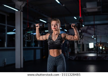 Beautiful muscular young woman doing exercises with dumbbells in the gym. The girl is working out the muscles of the arms with a dumbbell. Female bodybuilder trains biceps and triceps