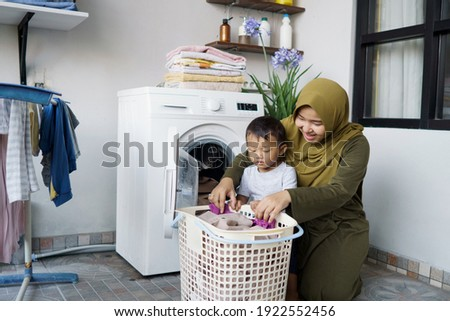 beautiful muslim asian woman doing laundry with her son together Foto d'archivio ©