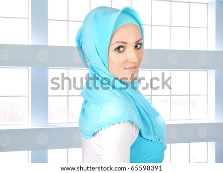 Beautiful Muslim fashion girl, islamic young business woman indoor, glass building