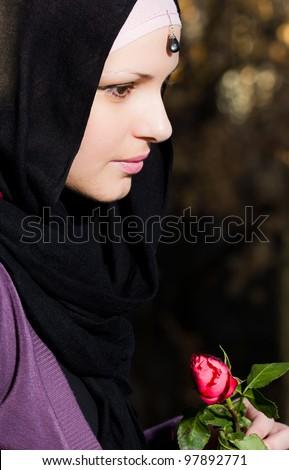 Beautiful muslim girl holding red rose flower