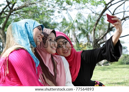 Beautiful Muslim girlfriends on picnic at sunny day - stock photo