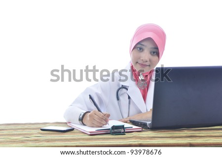 beautiful muslim medical doctor woman writting on note book in front of computer isolated on white background