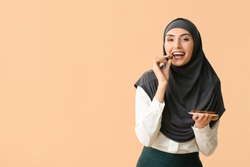Beautiful Muslim woman eating tasty chocolate candies on color background