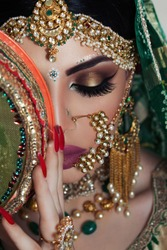 Beautiful Muslim Woman face portrait with bindis and paint.  Close up of beauty indian woman with perfect makeup and big green eyes. Traditional Maang Tikka , Nath,  Nose Pin