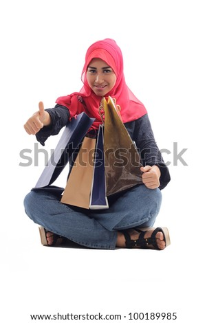 Beautiful muslim woman feel happy holding shopping bags with thumb up isolated on white