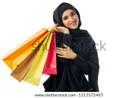 Beautiful Muslim woman in a black burqa Arab appearance hijab religion with packages in hands on a light background