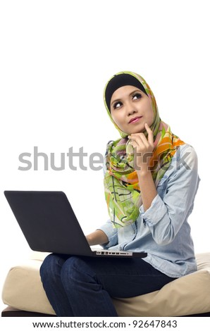 Beautiful muslim woman sitting in front of laptop and thinking