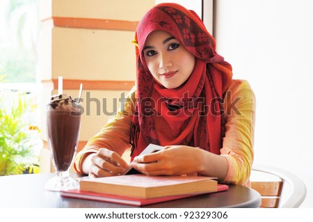 Beautiful muslim woman wearing red scarf smile while reading at the cafe #92329306